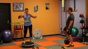 Client Hula Hooping while balancing on a BOSU helps develop balance and core strength.