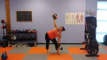 Client doing kettlebell hi-low Windmills develops core strength, shoulder stability and mobility.