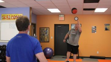 Client passes a medicine ball develops balance while standing on a BOSU.