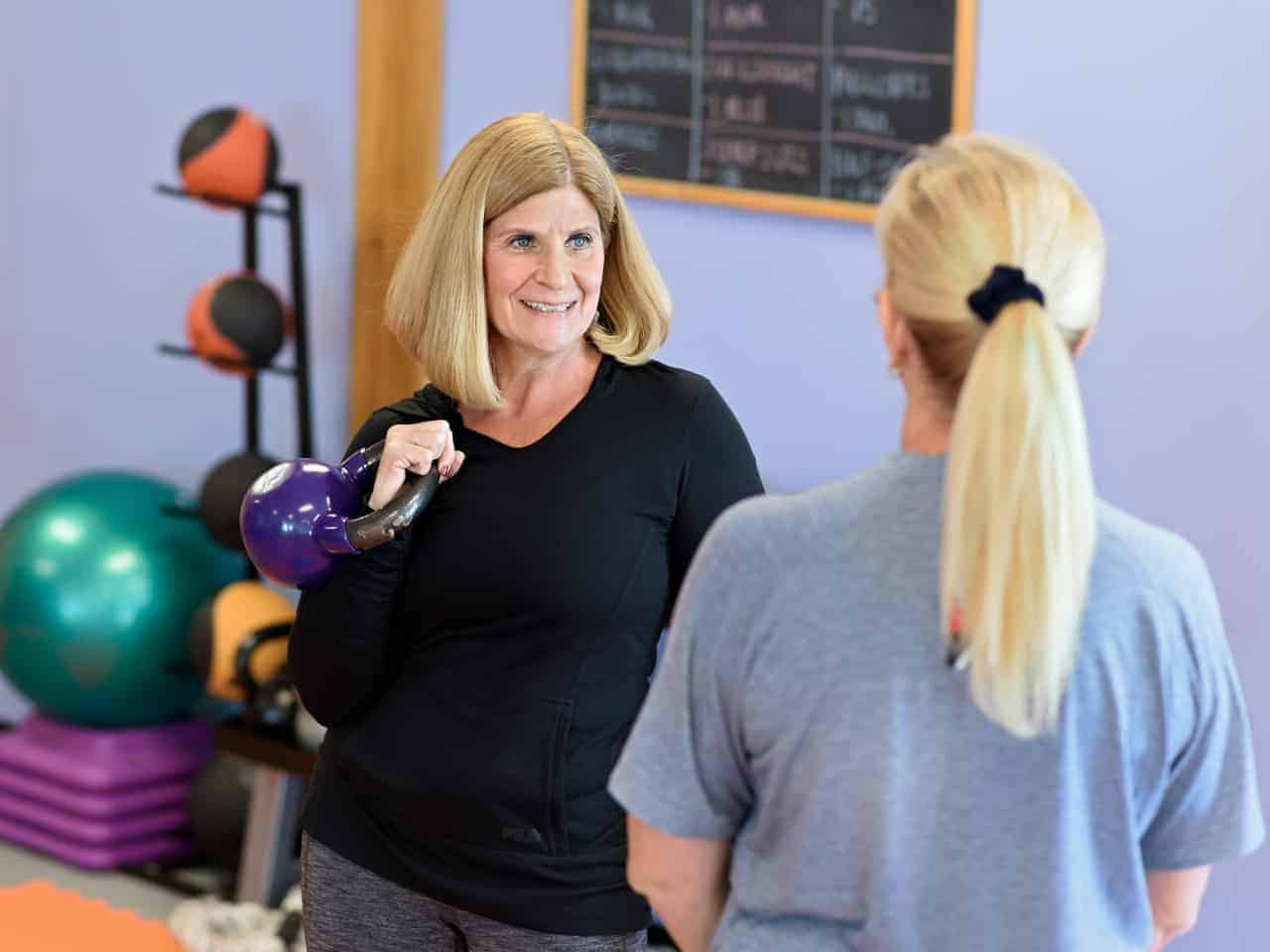 Personal Trainer demonstrates proper technique for holding a kettlebell.
