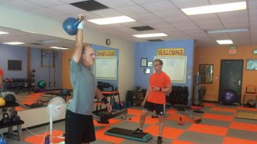 Client practices kettlebell overhead lockouts with a 14kg kettlebell as his personal trainer coaches.