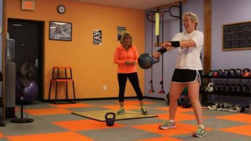Client practices 1-hand kettlebell swings with a 14kg kettlebell as her personal trainer coaches.