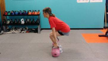 Kettlebell Training - client doing suitcase dead-lifts with kettlebells